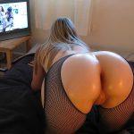 Rubia en medias de mallas viendo porno